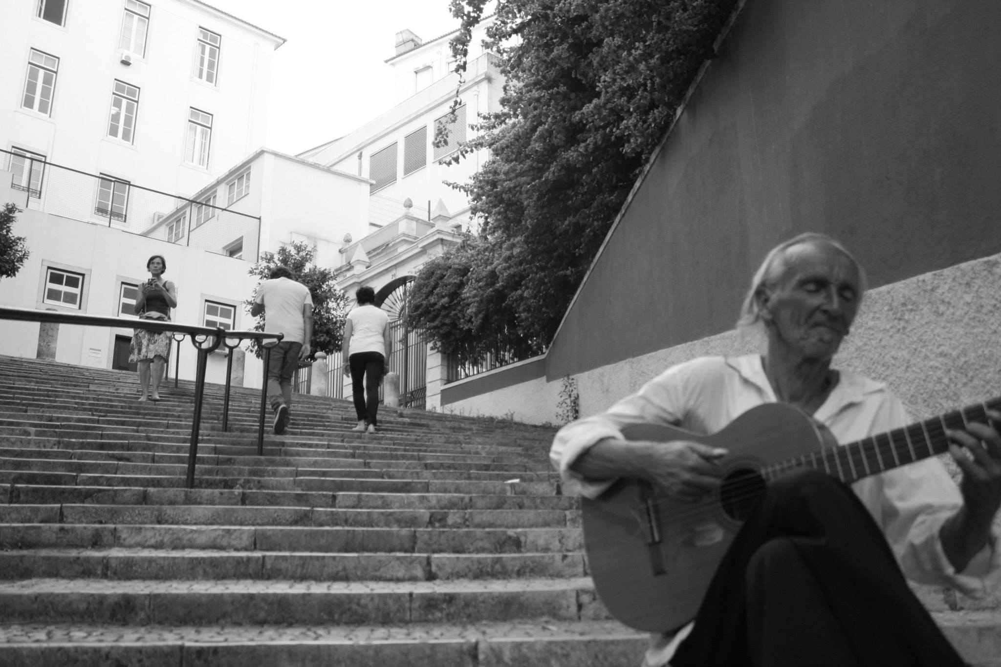 A man playing on his well-worn traveler classical guitar