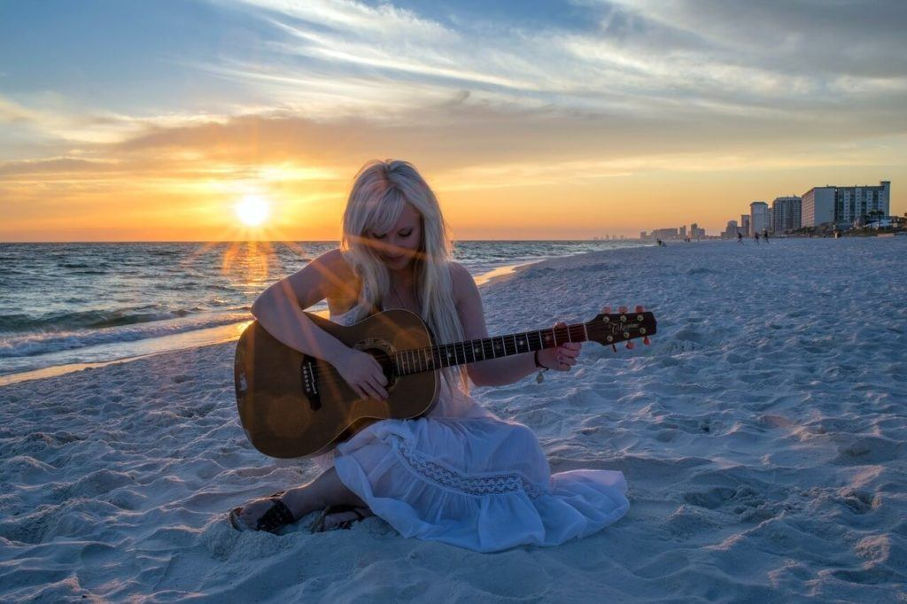Playing guitar at the beach is a free thing to do in the Sunshine Coast